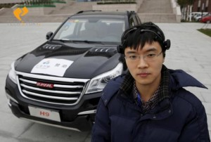Researcher Zhang Zhao wearing a brain signal-reading equipment poses with a vehicle which can be controlled with his brain wave