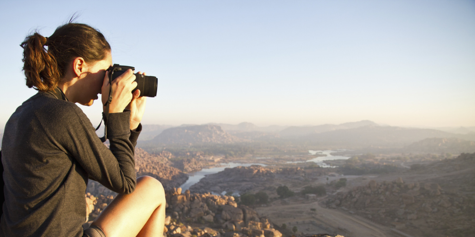 India, Karnataka, Young female tourist photographing on top of hill in Hampi