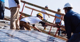Crew members for Grid Alternatives and Lifestyle Solar install solar panels on the roof of the home of the Hernandez family in Madera, California.