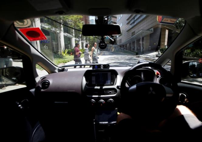 Pedestrians cross the road as a nuTonomy self-driving taxi undergoes its public trial in Singapore August 25, 2016. REUTERS/Edgar Su