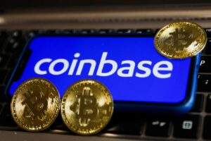 Coinbase logo displayed on a phone screen and representation of Bitcoin