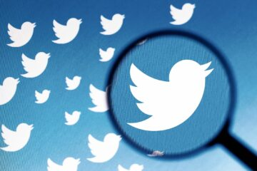 In this photo illustration a Twitter logo is seen on a computer screen through a magnifying glass