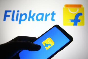 Flipkart logo of an Indian e-commerce company is seen on a smartphone and a pc screen