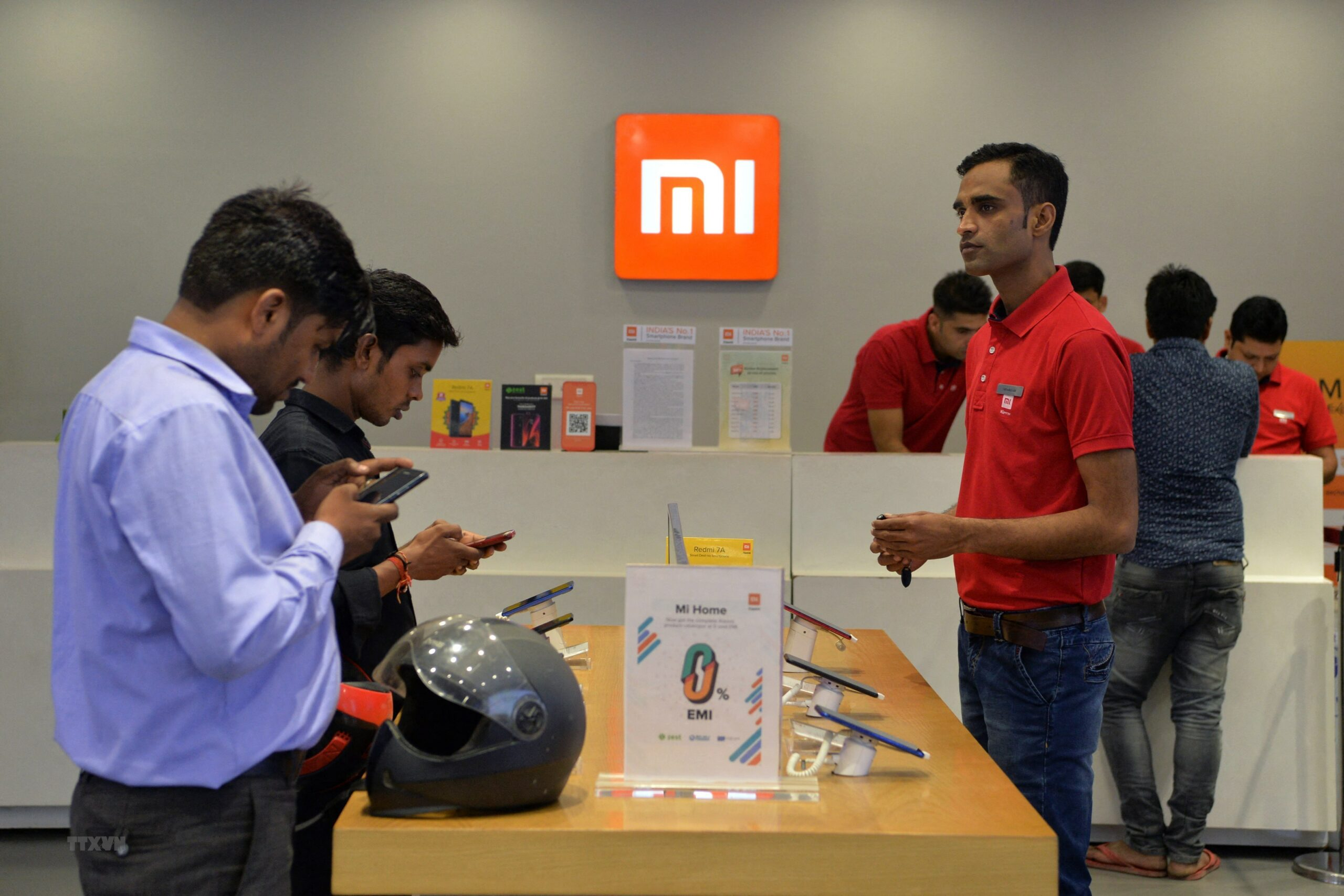Customers inspect smartphones made by Xiaomi at a Mi store in Gurgaon