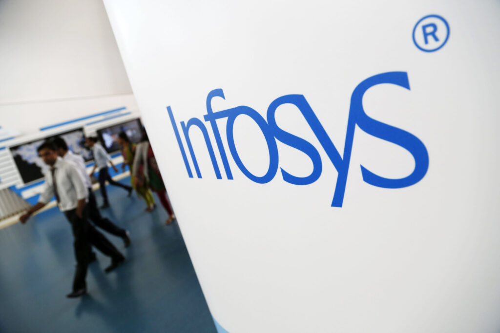 Employees walk past an Infosys Ltd. logo at the company's campus in Electronics City in Bangalore, India