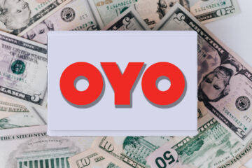 Pile of American banknotes and retro light box with OYO logo