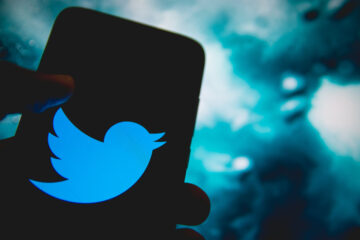Twitter logo is displayed on a smartphone screen