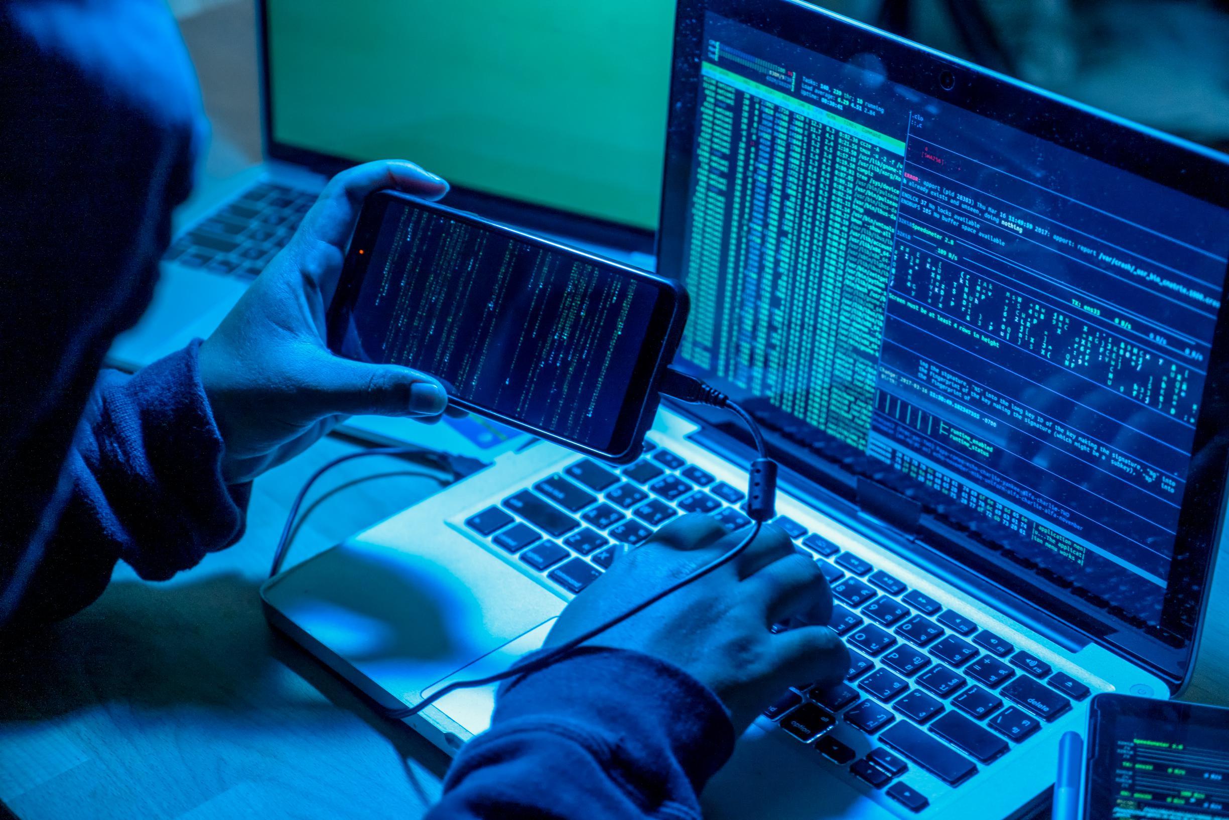 Hacker with computers in dark room