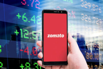 Zomato logo on a Smartphone; Abstract office Buildings and Trading Screen Data