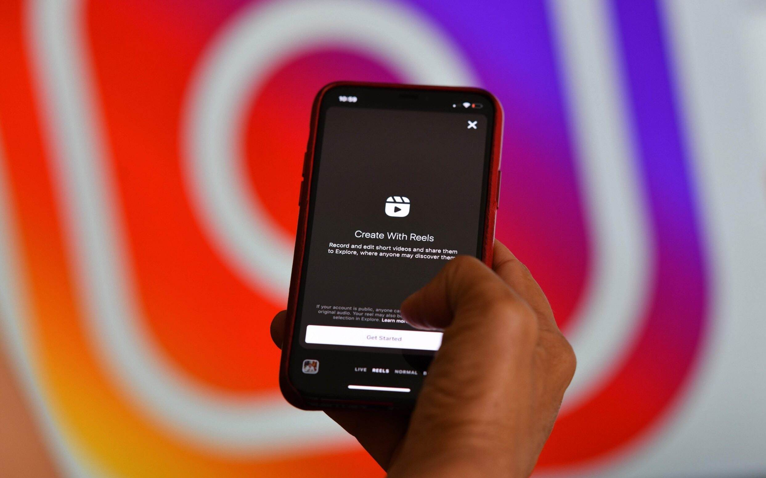"""Instagram's new video feature """"Reels"""" on a smartphone in front of a screen showing an Instagram logo"""