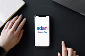 iPhone 11 placed on a table with Adani Super App mockup logo