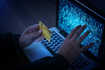 Hands of anonymous hackers holding credit card