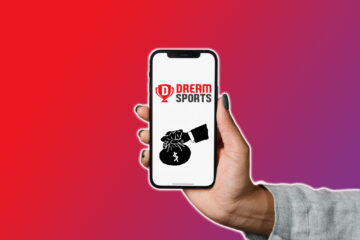 A woman holding smartphone in her hand with Dream Sports logo on it
