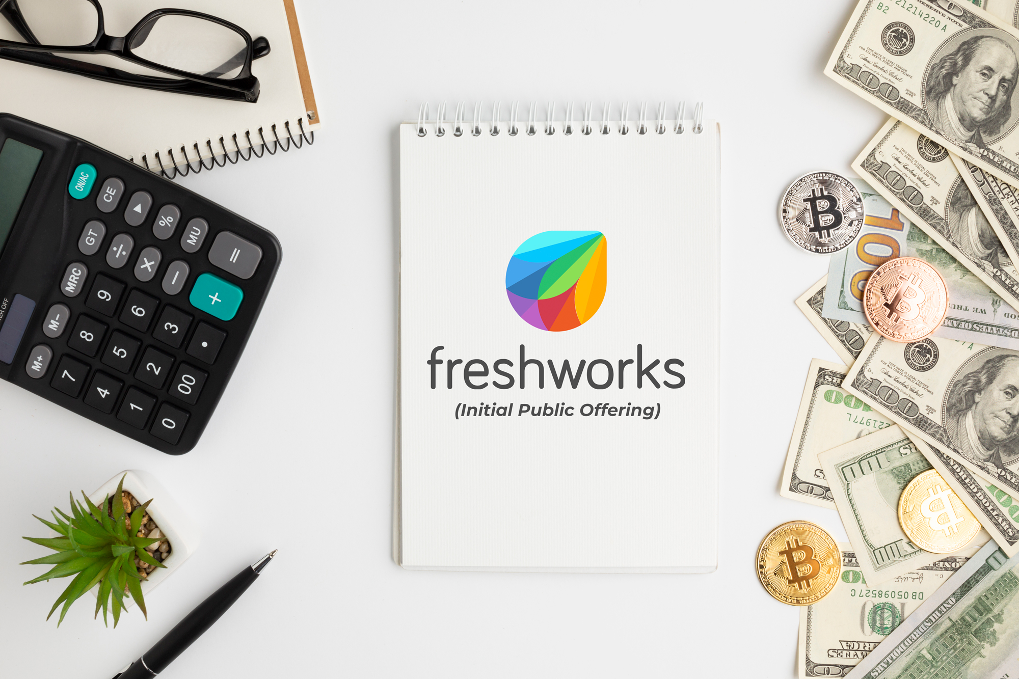 Table top view Freshworks logo in middle with a calculator on left and and US Dollar on right