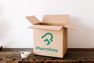 PharmEasy Cardboard box on dark wooden table near tape and scissors
