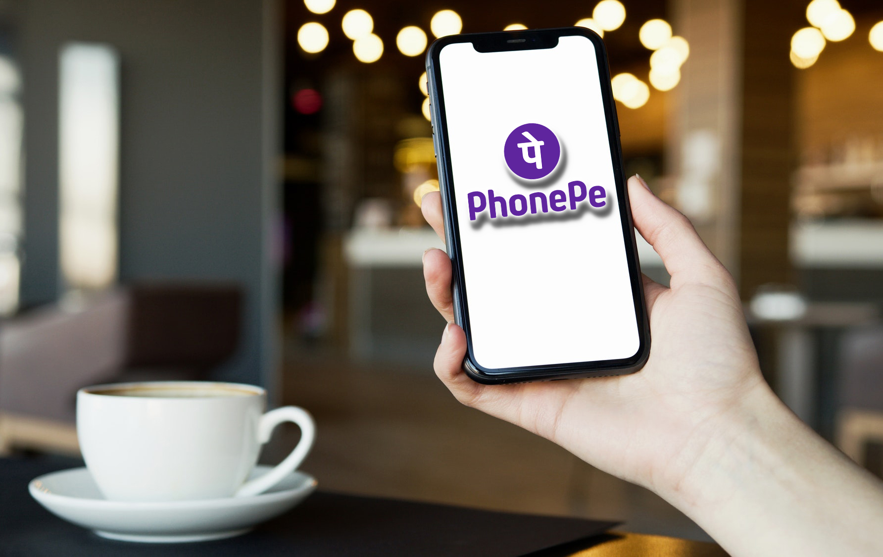 A person paying using PhonePe app at a Coffee Shop