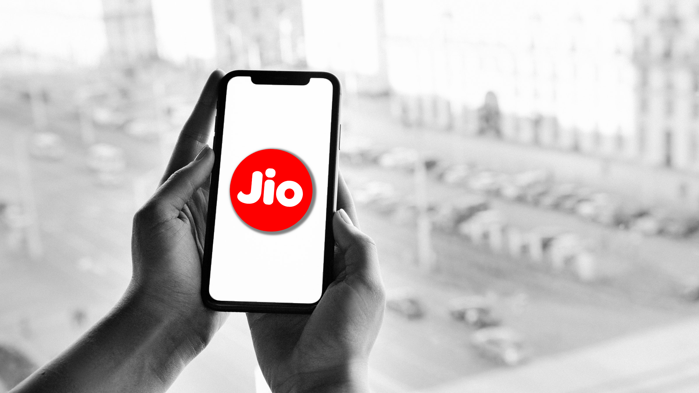 Grayscale Photo of Person Holding Smartphone with Jio Logo