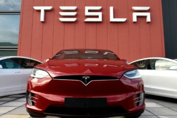 Red Tesla car outside showroom