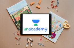 Unacademy Logo on iPad with Paper Clips and Erasers Flatlay
