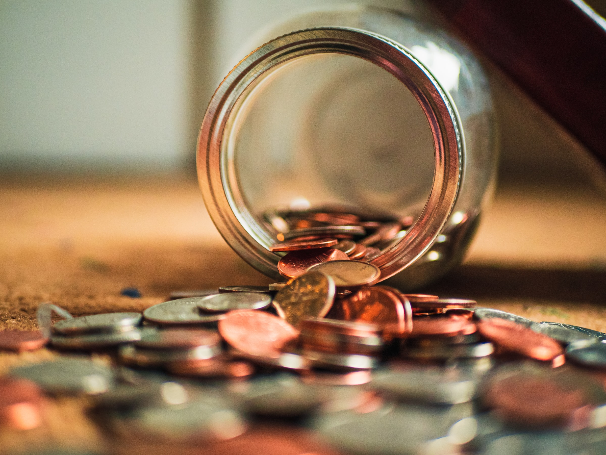 Coins falling from a glass jar
