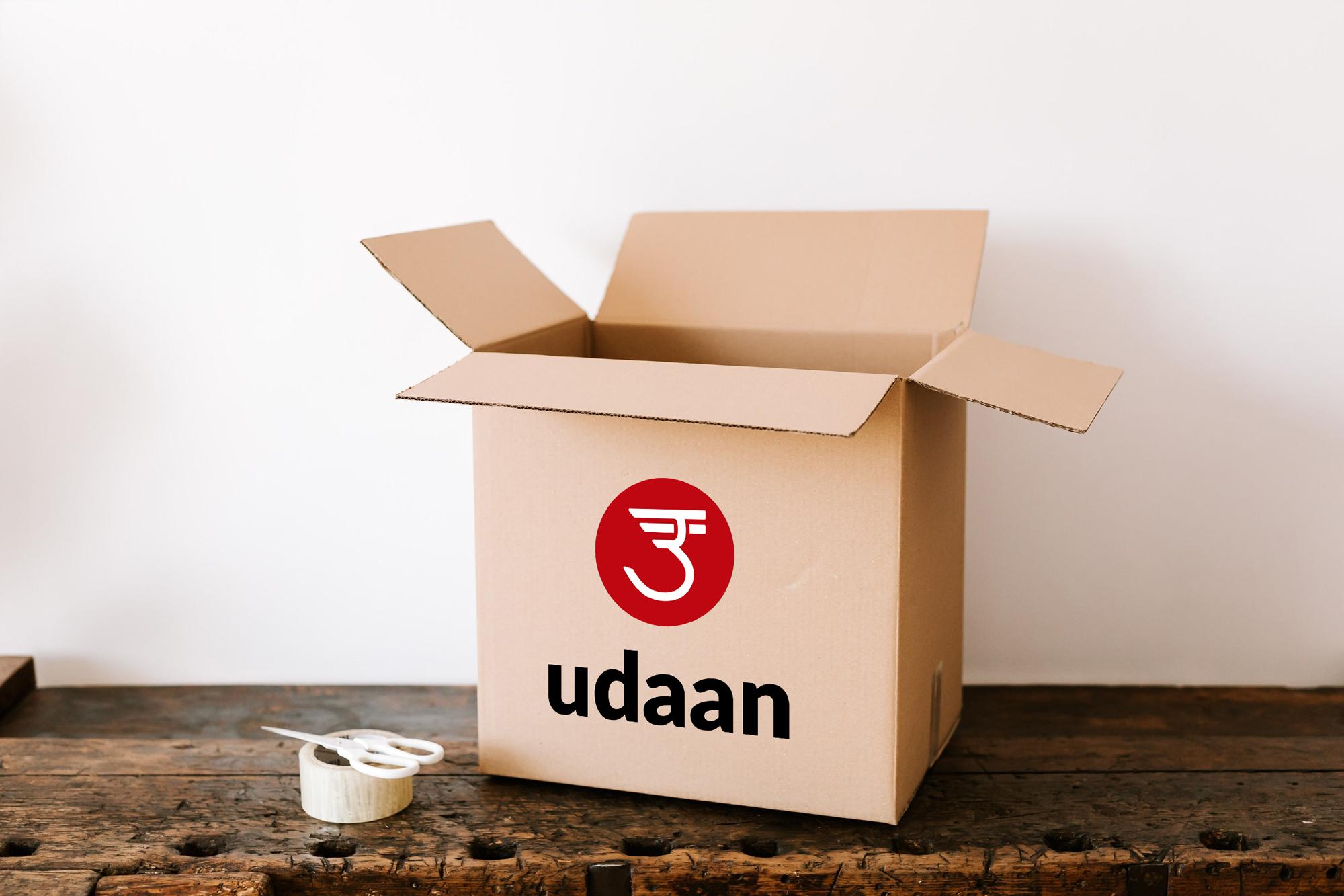 Udaan box on dark wooden table near tape and scissors