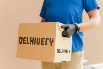 Person holding Delhivery Courier box