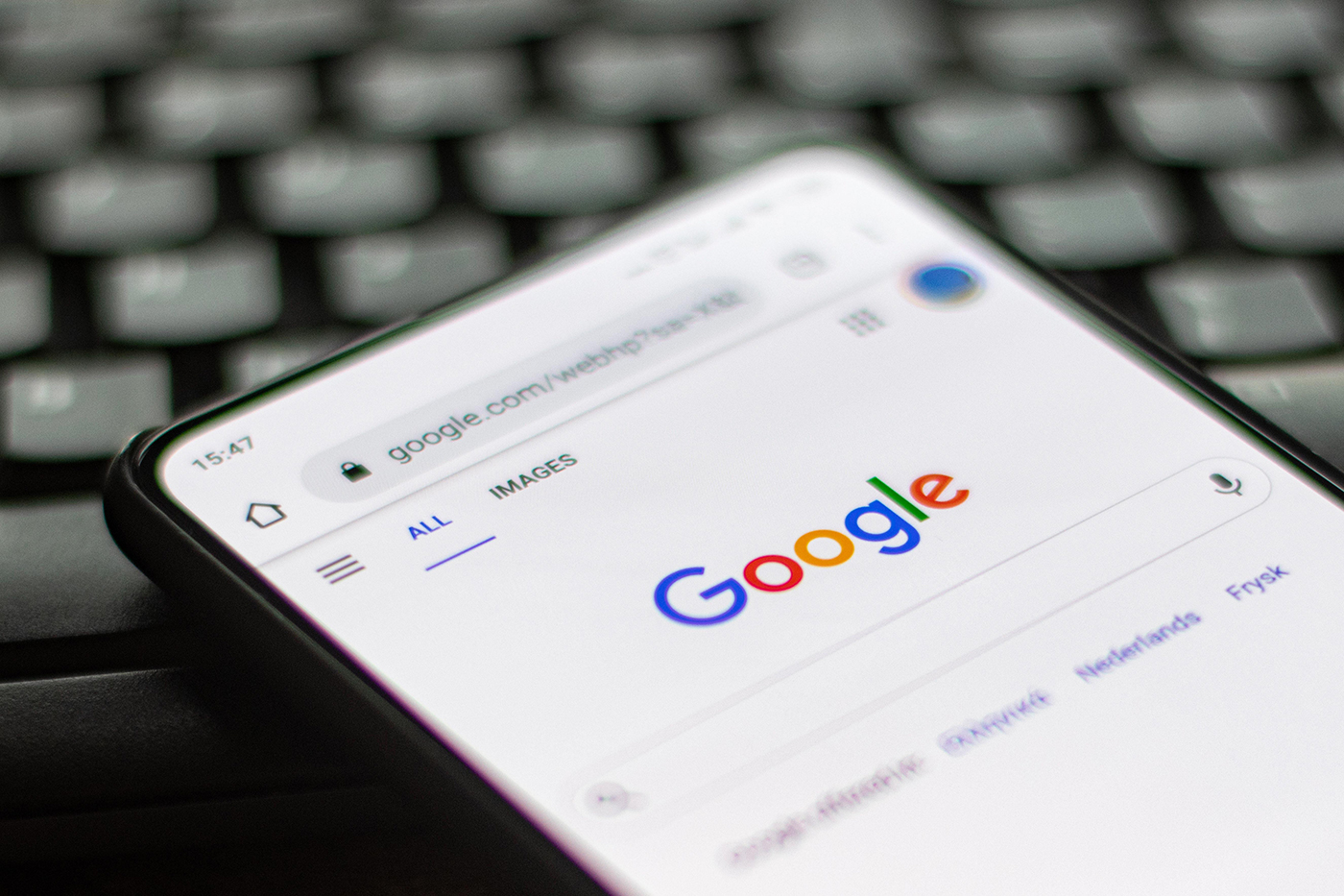 Google closeup logo displayed on a phone screen, smartphone on a keyboard is seen in this multiple exposure illustration, the company's symbol is globally recognized