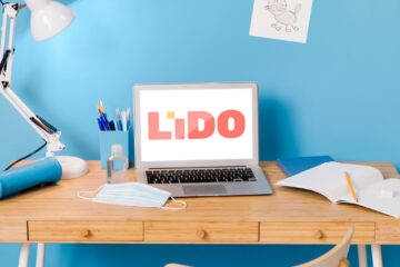 Front view of school desk with laptop displaying Lido Learning logo and lamp