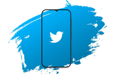 twitter logo displayed on a smartphone with blue splash background