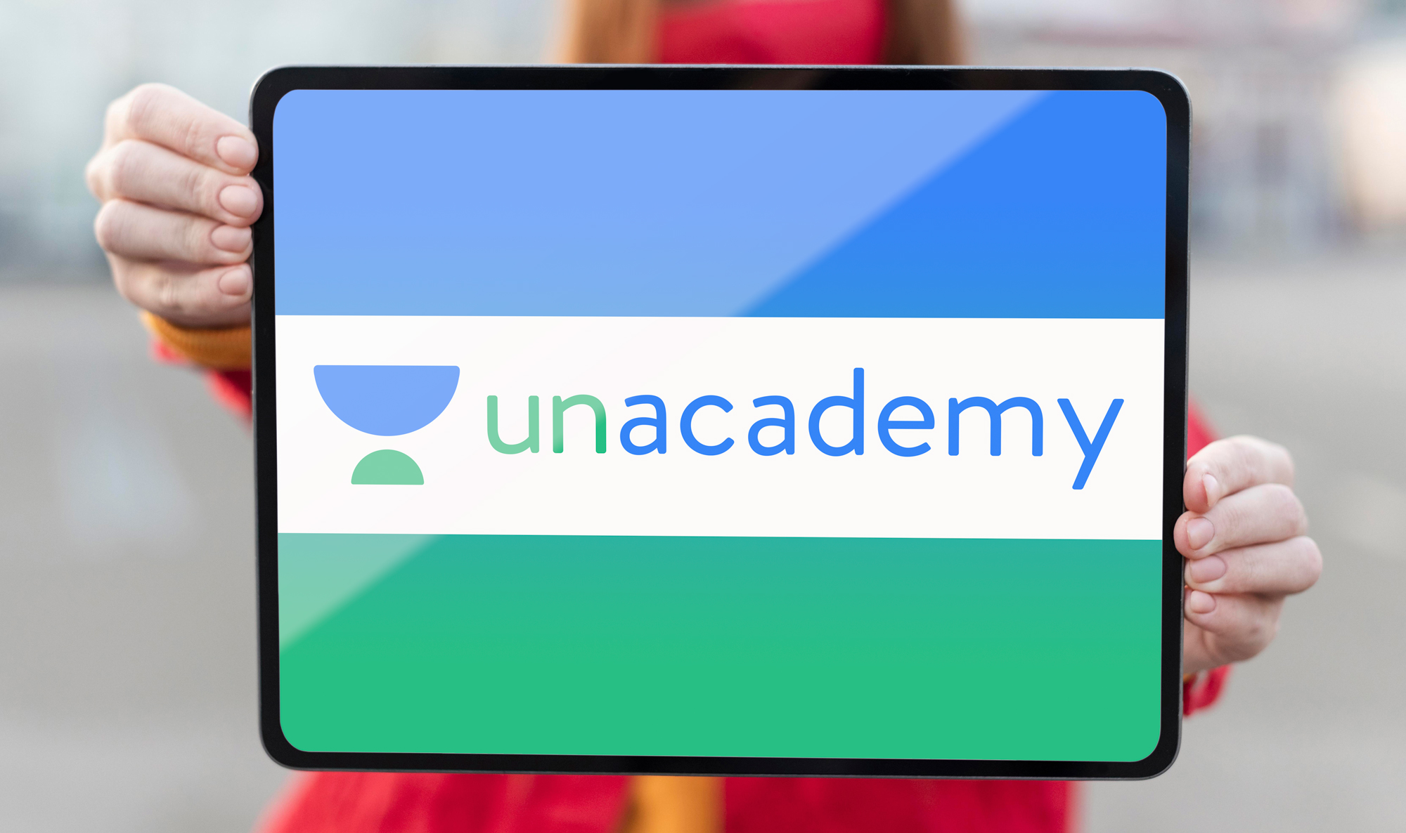 woman holding a tablet displaying Unacademy logo