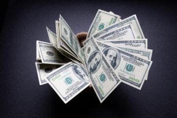 American dollars cash money in sack on black table in the dark room