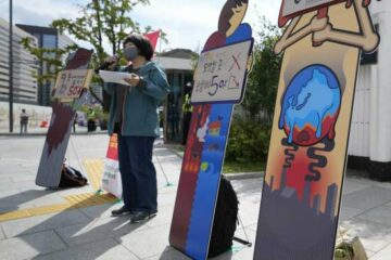 """An environmental activist speaks during a press conference on the effort to curb greenhouse gas emissions as part of the climate strike in Seoul, South Korea, Friday, Sept. 24, 2021. The banners read: """"Greenhouse gas, 50 percent down."""""""