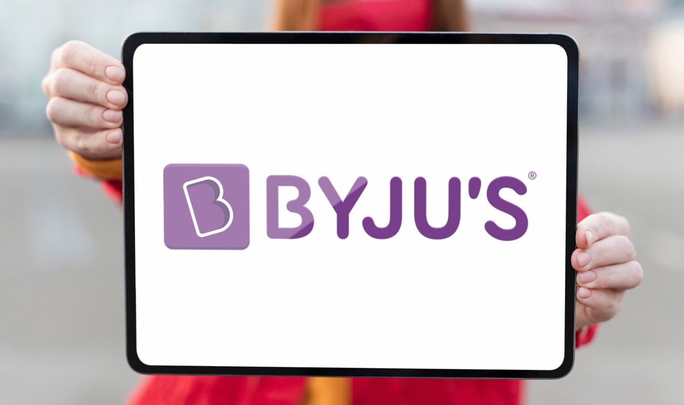 Byju's logo displayed on a tablet held by Redhead woman