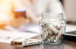 A jar with rolled banknotes on the table
