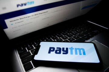 Paytm logo displayed on a phone screen and Paytm website displayed on a laptop screen are seen in this illustration